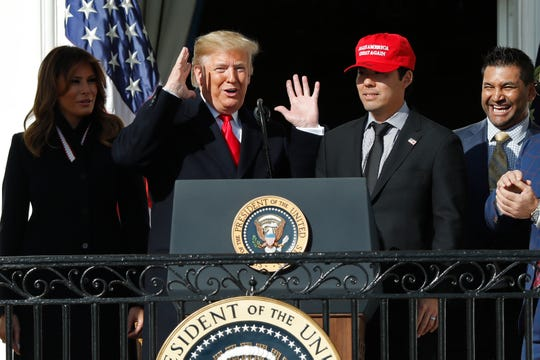 President Donald Trump, left, is happy to welcome Kurt Suzuki to the microphone during Monday's celebration of the Nationals' World Series victory.