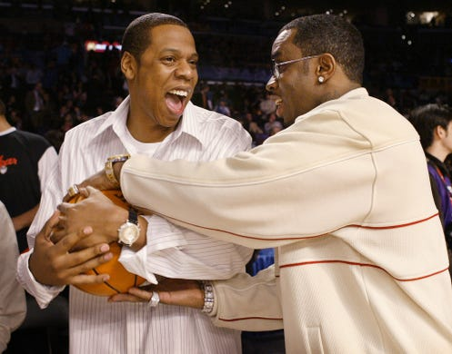 Fellow New York rapper and businessman Jay-Z jokes with Diddy before the start of the NBA All-Star game in Los Angeles on Feb. 15, 2004.