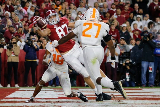Alabama tight end Miller Forristall tries to pull in a reception as Tennessee  linebacker Quavaris Crouch defends.