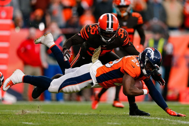 Denver Broncos running back Royce Freeman (28) is tripped up running the ball as Cleveland Browns safety Jermaine Whitehead (35) defends in the third quarter at Empower Field at Mile High.