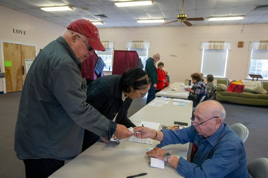 Jim and Dee Grossi of Toms River sign in with Victor Goldfarb of Manchester, a poll worker, before casting their vote on Election Day at the First United Methodist Church in Toms River, NJ Tuesday, November 5, 2019.