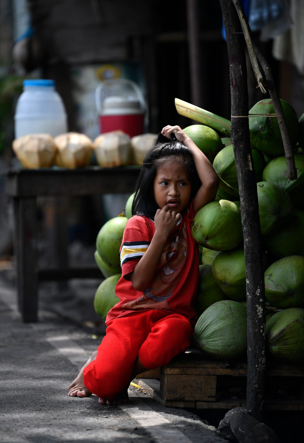 A young girl leans into a stack of coconuts as she ties her hair at a roadside stand along the Bataan Provincial Highway in the Philippines Oct. 20, 2019. The road is the same one taken by American and Filipino prisoners of war during the infamous Bataan Death March in April 1942.