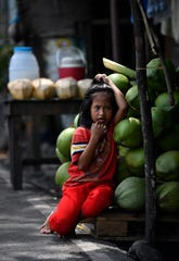 A young girl leans into a stack of coconuts as she ties her hair at a roadside stand along the Bataan Provincial Highway on Oct. 20. The road is the same one taken by American and Filipino prisoners of war during the infamous Bataan Death March.