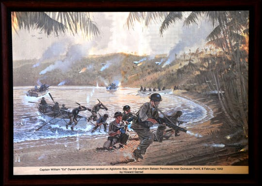 "A framed illustration by Howard Gerrad of Capt. William ""Ed"" Dyess charging the beach at Bataan's Aglolomo Bay in the Philippines Feb. 8, 1942, on display in the Bataan World War II Museum in Balanga City. During the fight for Bataan, Dyess' 21st Pursuit Squadron had to give up their planes for other squadrons to use elsewhere. His men trained as a mobile infantry unit during this time, defending the peninsula against Japanese invaders."