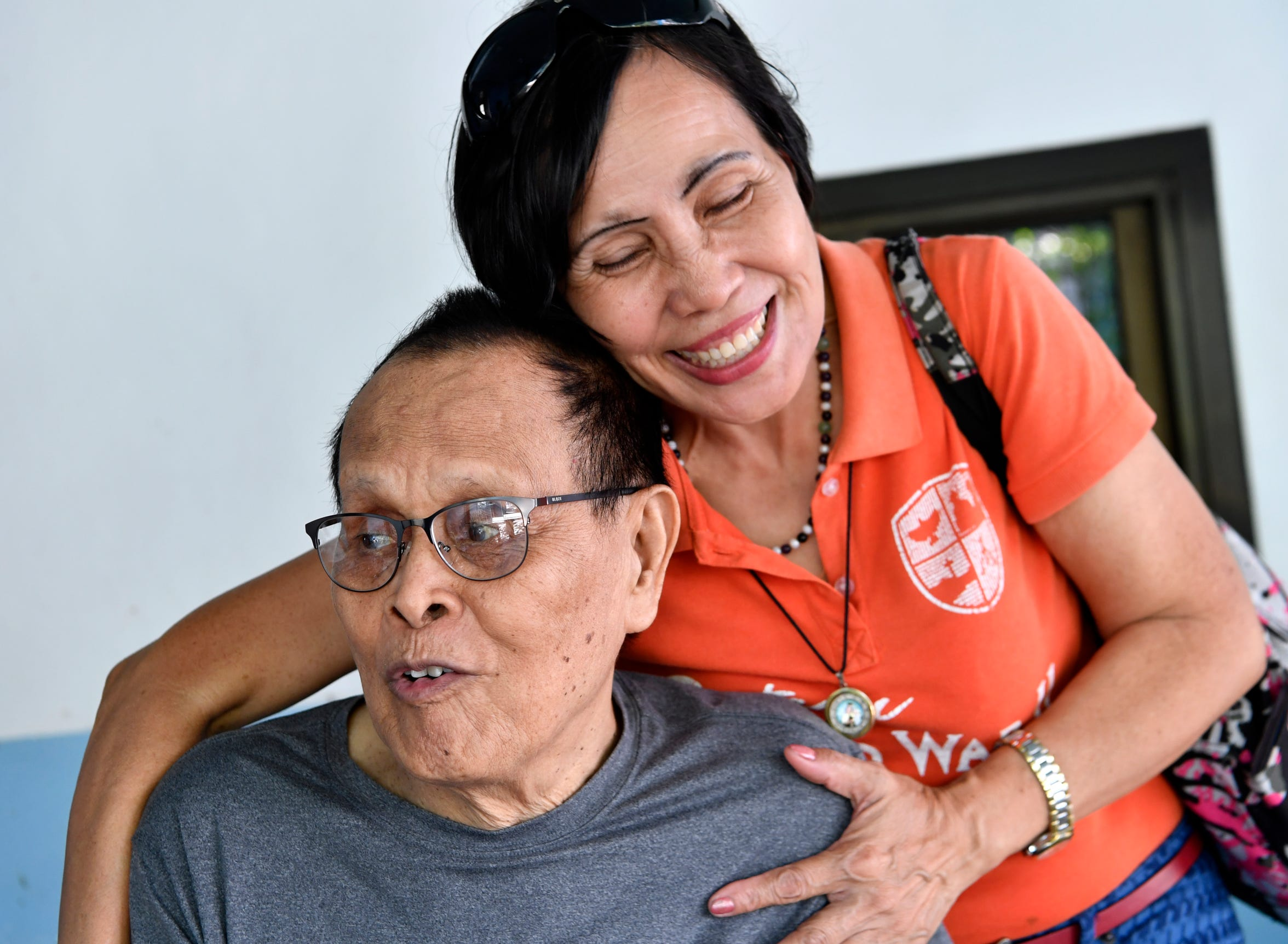 Katherine Mejia gives Nestor Ceniza a hug at his home in Balanga City, Philippines, on Oct. 21, 2019. Mejia is the key holder, or director, of the Bataan World War II Museum, Ceniza is a survivor of the concentration camp at Camp O'Donnell during the Japanese occupation of the Philippines.