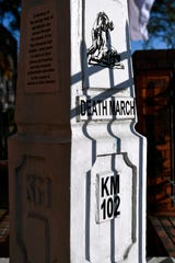 A low sun casts shadows upon a Bataan Death March marker in front of the San Fernando train station in the Philippines. The markers are found regularly along the entire route of the World War II forced march of American and Filipino soldiers.