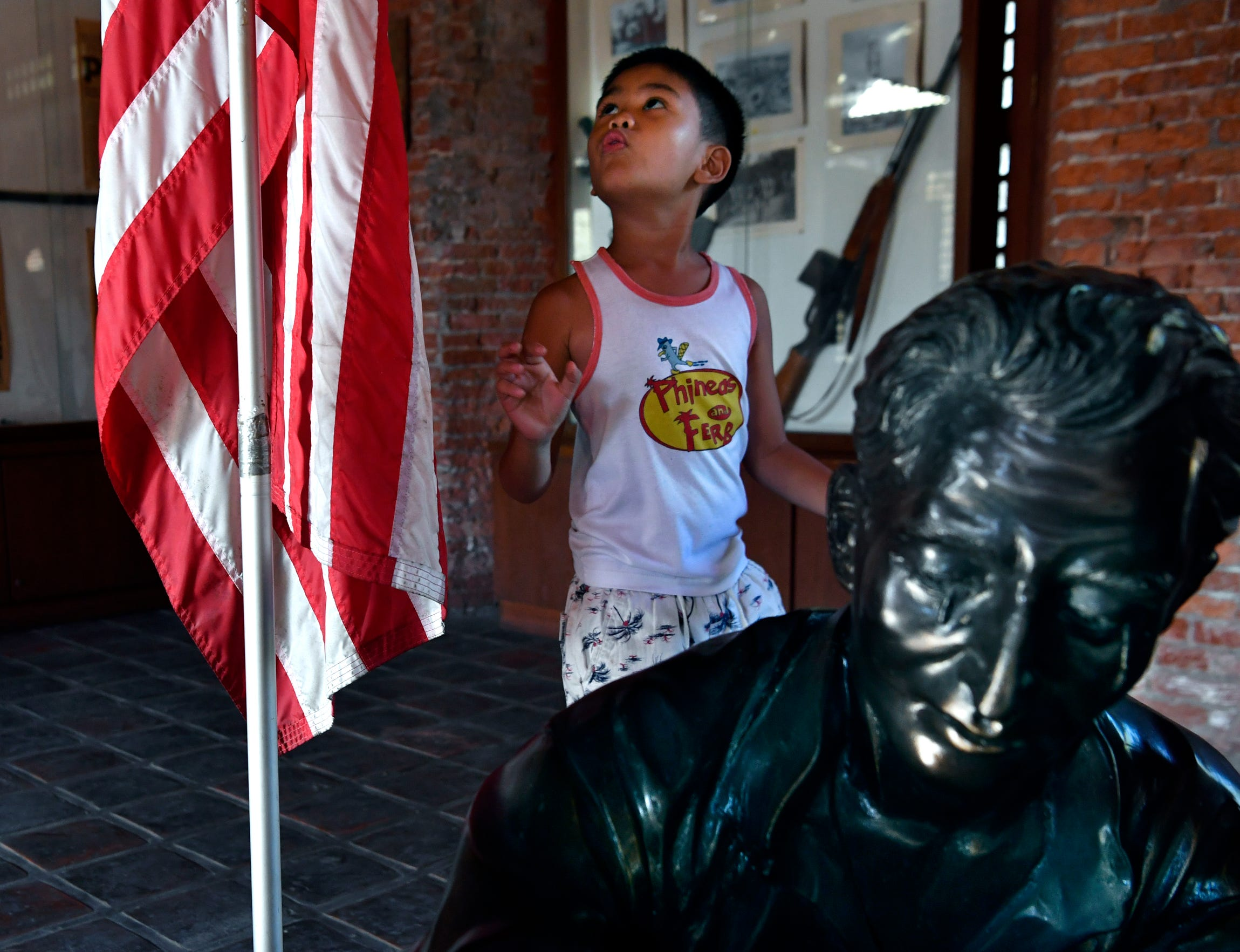 A young boy looks up at the American flag as he walks past statues depicting American and Filipino prisoners of war in the San Fernando train station Oct. 21, 2019, Philippines. The station is where American and Filipino soldiers were loaded into boxcars and sent north to prison camps during Word War II. The station is now a museum.