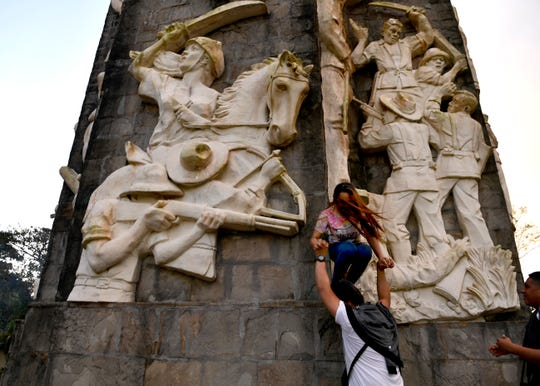 Visitors set themselves up for a picture beneath Mount Samat National Shrine in Pilár, Bataan, Philippines on Oct. 20. The monument, a 311-foot cross, is part of a memorial dedicated to the defenders of Bataan during World War II.