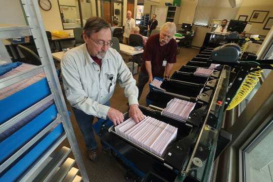 Election workers Harry Turnbull, left, and Rodney Kent place ballots into bins as a machine sorts them by precincts at the Kitsap County Auditor's Office on Tuesday.