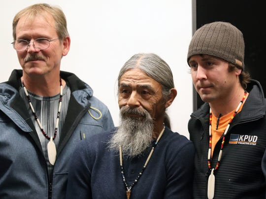 David Sigo, center, is flanked by Carl Wodenscheck, left, and Chad Waag, right, as they pose for photos for family members at North Kitsap Fire and Rescue in Kingston on Monday. Both Wodenscheck and Waag helped NKFR locate Sigo after he was tangled in his fishing net and swept overboard on Oct. 23.