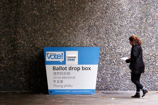A voter heads to a ballot drop box Monday, Nov. 4, 2019, in Seattle. Voters in Washington state have a crowded ballot to fill out for this week's election, with a referendum on affirmative action and an initiative on the price of car tabs among the things they are being asked to decide.