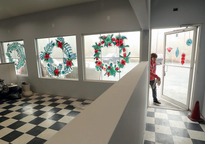 Christmas window paintings that were done before the tornado hit in 2018 still adorn the windows as Shari Patrick enters the front door of her Ruby Slipper Bar & Grill, located in the Bethel Square complex in Port Orchard. Nearly 11 months after the Dec. 18, 2018, tornado hit, Patrick can see the light at the end of the tunnel of reconstruction.