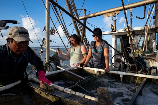 Caller-Times reporter Kathryn Cargo (center) snaps a photo on a shrimp boat during coverage about the state of the industry in South Texas.