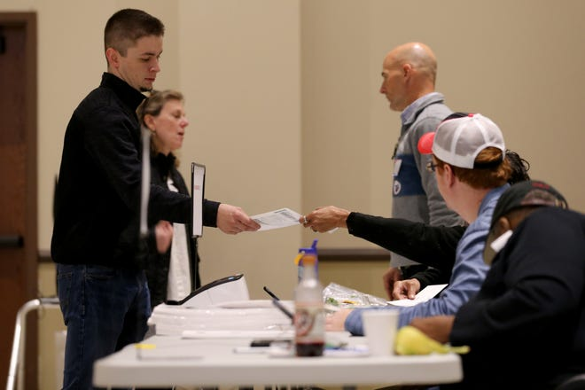 Poll workers distribute ballots to voters, Tuesday, Nov. 5, 2019, at Knox Presbyterian Church in Hyde Park.