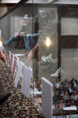 Residents sitting in the extra seating in the balcony flip over their signs they had lean up against the glass facing county commissioners at the commission meeting discussing the new events center at Montgomery County Historic Courthouse in Clarksville, Tenn., on Monday, Nov. 4, 2019.