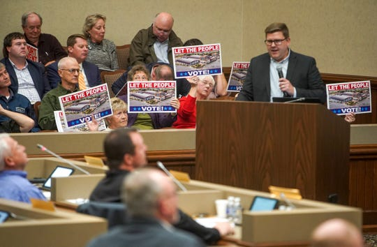 Residents hold up signs in support of the proposed events center behind speakers during a county commission meeting at Montgomery County Historic Courthouse in Clarksville, Tenn., on Monday, Nov. 4, 2019.