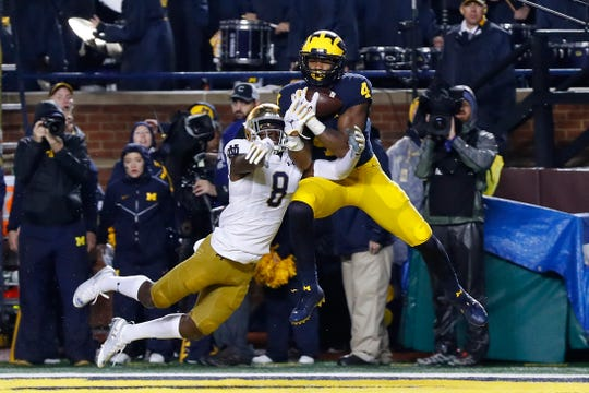 Nico Collins catches a 16-yard touchdown pass over Notre Dame's Donte Vaughn in Ann Arbor, Oct. 26.