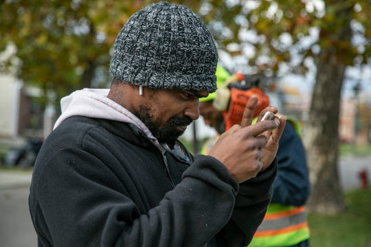 Leonard Fantroy, 41, of Detroit, who is legally blind, struggles to see his phone screen while on a work site with his landscaping business.