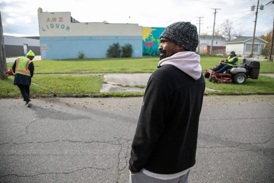Leonard Fantroy, 41, of Detroit looks on as his employees cut a lawn for a client in Detroit on Tuesday, Nov. 5. Fantroy, who is legally blind,  began to lose his eyesight in prison in 2014. He started his own business last year after deciding not to return to a life of selling drugs.