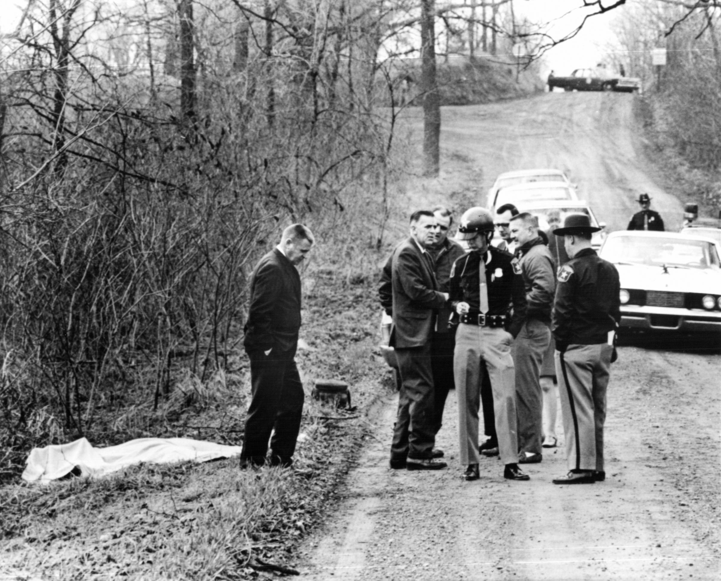 Washtenaw County Sheriff's onfer on a rural road north of Ypsilanti where the body of a 13-year old was found in April, 1969. Dawn Basom of Ypsilanti, whose nude body lies under the blanket at left, was the fifth young woman to be murdered in the Ann Arbor-Ypsilanti Area in the past 22 months. None of the murders have been solved.
