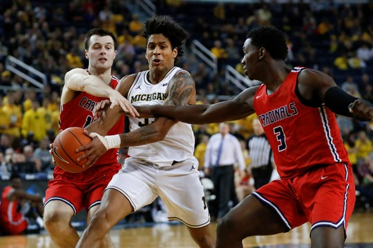 Michigan's Eli Brooks drives between Saginaw Valley State's James Toohey, left, and Myles Belyeu (3) during the second half in Ann Arbor, Nov. 1, 2019.