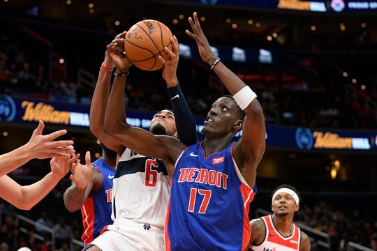 Detroit Pistons forward Tony Snell (17) battles for the ball next to Washington Wizards guard Troy Brown Jr. (6).