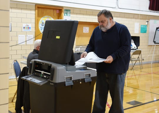Sonny Eplin, 63, of Eastpointe prepares to insert his ballot into the tabulator after voting at Forest Park Elementary School Tuesday.