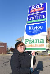 Volunteer Barbara Winter of Hazel Park, stands outside the Ferndale Public Library   with signs supporting her candidates.