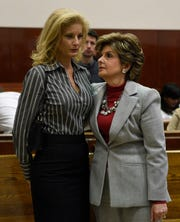 "Summer Zervos, left, a former contestant on the television show ""The Apprentice,"" listens to her lawyer Gloria Allred in New York County Criminal Court in this December 5, 2017, file photo."