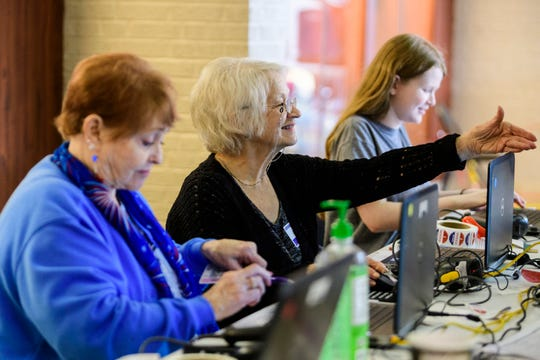 Poll worker Bonnie Sullivan, center, asks a voter for their photo identification as Brandy Devine, front, Kailey Powers, back, also check in other voters at Plaza Park International Prep Academy in Evansville, Tuesday morning, Nov. 5, 2019.