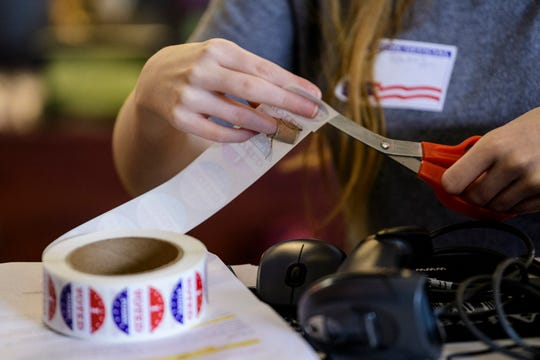 """Poll worker Kailey Powers snips out """"I voted"""" stickers to give out at Plaza Park International Prep Academy in Evansville, Tuesday morning, Nov. 5, 2019."""