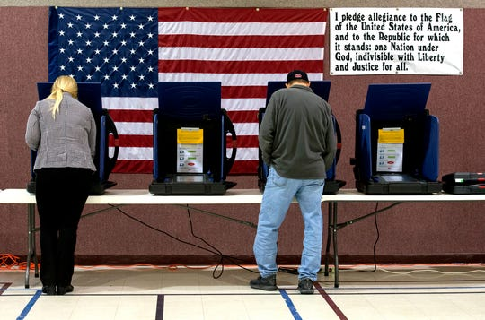 Voters Katie Stahl, left, and Scott Hayes ,right, cast their ballots at St. James United Methodist Church Tuesday evening, Nov. 5, 2019.