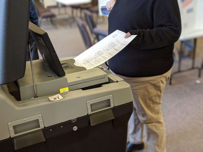 A voters submits a ballot at Grace Community in Ballville Township.