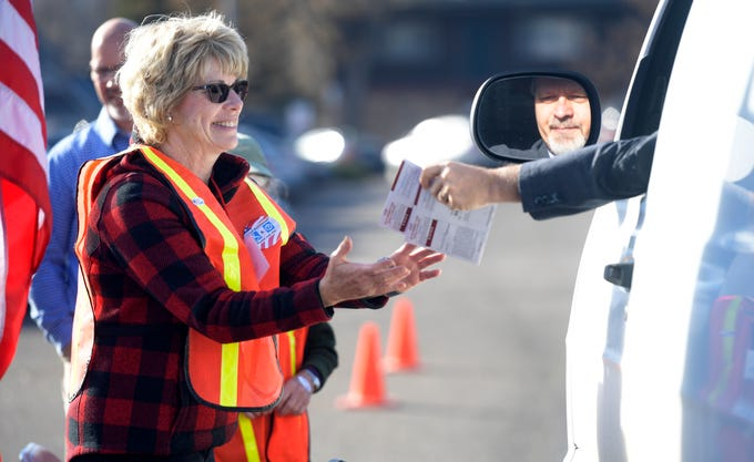 A volunteer accepts ballots from a driver in the drive-thru ballot drop off across from the Larimer County Courthouse in Fort Collins, Colo. on Tuesday, Nov. 5, 2019.
