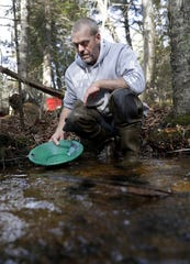Jason Kelter of Abrams pans a sample of sediment in a creek near Silver Cliff to separate black sand and flour gold.