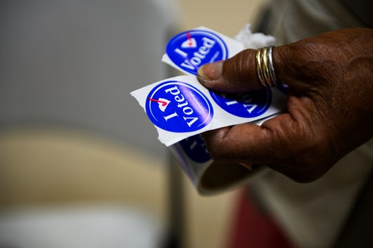 "Charity Jones holds a roll of ""I voted"" stickers for voters at the Brutontown Community Center Tuesday, Nov. 5, 2019."