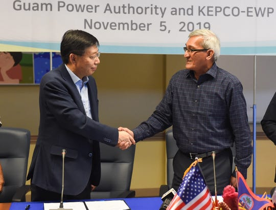 John Benavente, Guam Power Authority general manager, right, shakes hands with Guen Bae Seo Korea Electric Power Corporation vice president and head of the Global Business Development Department, following the contract signing of the Ukudu Power Plant Plant, in the Gloria B. Nelson Public Service Building, Mangilao, Nov. 5, 2019.