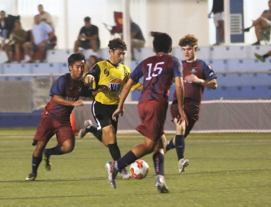 The NAPA Rovers FC's Dylan Naputi attempts to weave through the Bank of Guam Strykers defense in a Week 3 Premier Division match of the Budweiser Soccer League Saturday at the Guam Football Association National Training Center. The Strykers won 3-2.