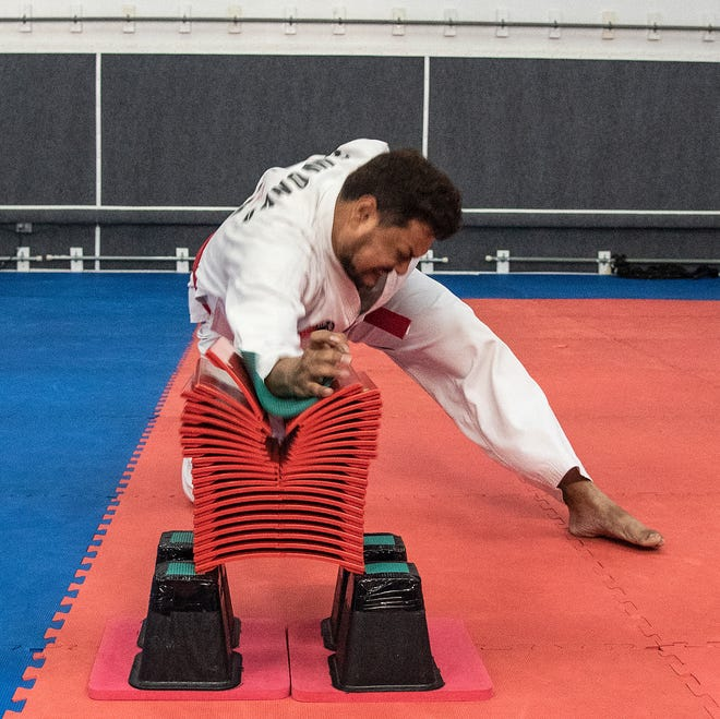 Guru Chattaraj, a red belter from Guam Taekwondo Center practices his breaking skills with a stack of tiles during practice.