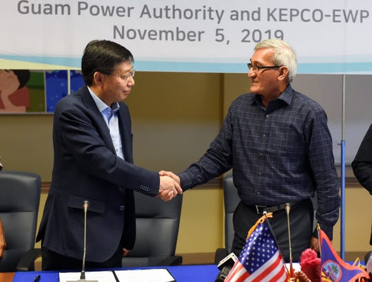 John Benavente, Guam Power Authority general manager, right, shakes hands with Guen Bae Seo, Korea Electric Power Corporation vice president and head of the Global Business Development Department, following the contract signing of the Ukudu Power Plant Plant, in the Gloria B. Nelson Public Service Building, Mangilao, Nov. 5, 2019.