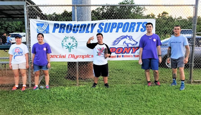 Members of the Special Olympics Guam PONY Champions Softball League stand in front of a sponsor banner following a workout.