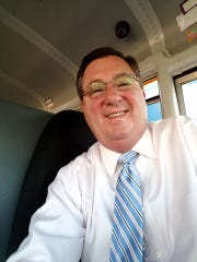 Bob Walters, former PR director at IMS, sits on the school bus he drives for HSE Schools.