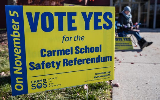 Lisa McLaughlin, a Carmel resident, sits outside to answer any questions about the Carmel School Safety Referendum for any voters entering the Education Services Center voting site in Carmel, Ind., on Tuesday, Nov. 5, 2019.