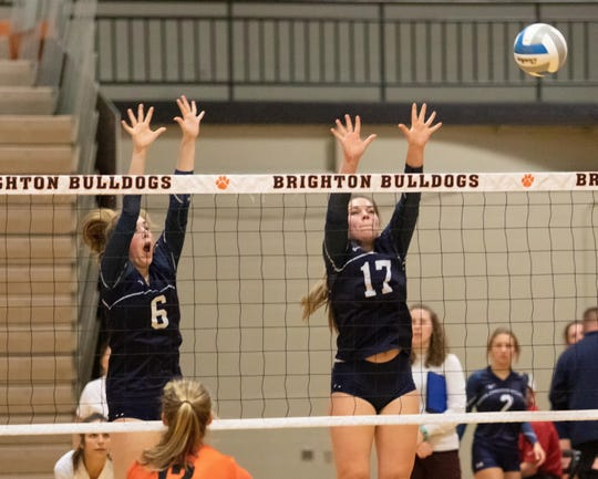 Emma Francisco (6) and Madison Candela (17) of Hartland go for a block against Brighton in a district volleyball match on Monday, Nov. 4, 2019.