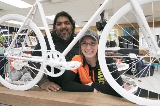 """Shaun and Dawn Bhajan peer through the """"Ghost Bike"""" on display at their Brighton Township store, Hometown Bicycles, Tuesday, Nov. 5, 2019. The bike is in memory of Daniel J. Horal, who died after being hit by a car in the Island Lake State Recreation Area."""