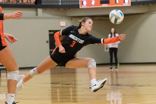Evelynn Lemons of Brighton reaches for the volleyball in a district match against Hartland on Monday, Nov. 4, 2019.
