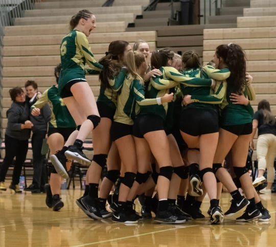 Howell volleyball players celebrate their victory over South Lyon East in a first-round district match at Brighton on Monday, Nov. 4, 2019.