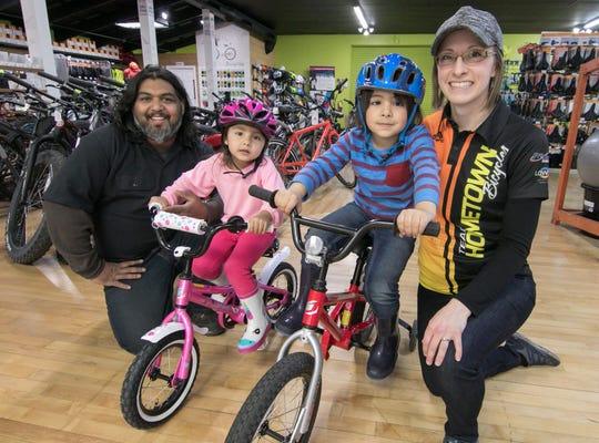 """Shaun Bhajan and his wife Dawn, with their two children, 3-year-old Aria, and 4-year-old Liam, own Hometown Bicycles, shown Tuesday, Nov. 5, 2019, a Brighton Township store voted """"Michigan Shop of the Year"""" by the League of Michigan Bicyclists."""