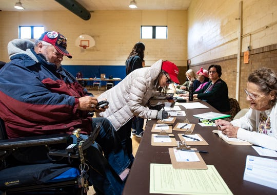 Edgar Russell, left, and wife Sophia, middle, check in to vote Tuesday, Nov. 5, 2019, at Foster Community Center in Lansing.