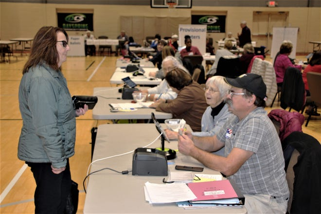 Poll workers assist a resident preparing to vote at Dayspring Wesleyan Church on Election Day. Poll workers there said a steady flow of voters passed through the church gymnasium throughout the morning and early afternoon hours on Tuesday.